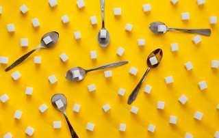 Refined Sugar Cubes And Teaspoons Shot On A Yellow Background. B